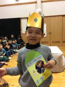 所沢市のあかねの虹保育園の2月のお誕生日会にて、担任の先生からメッセージカードのプレゼントをもらい、嬉しそうな子どもの画像