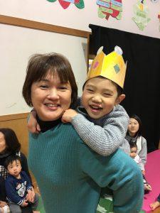 所沢市のあかねの虹保育園の2月のお誕生日会にて、園長先生におんぶしてもらい嬉しそうな子どもの画像