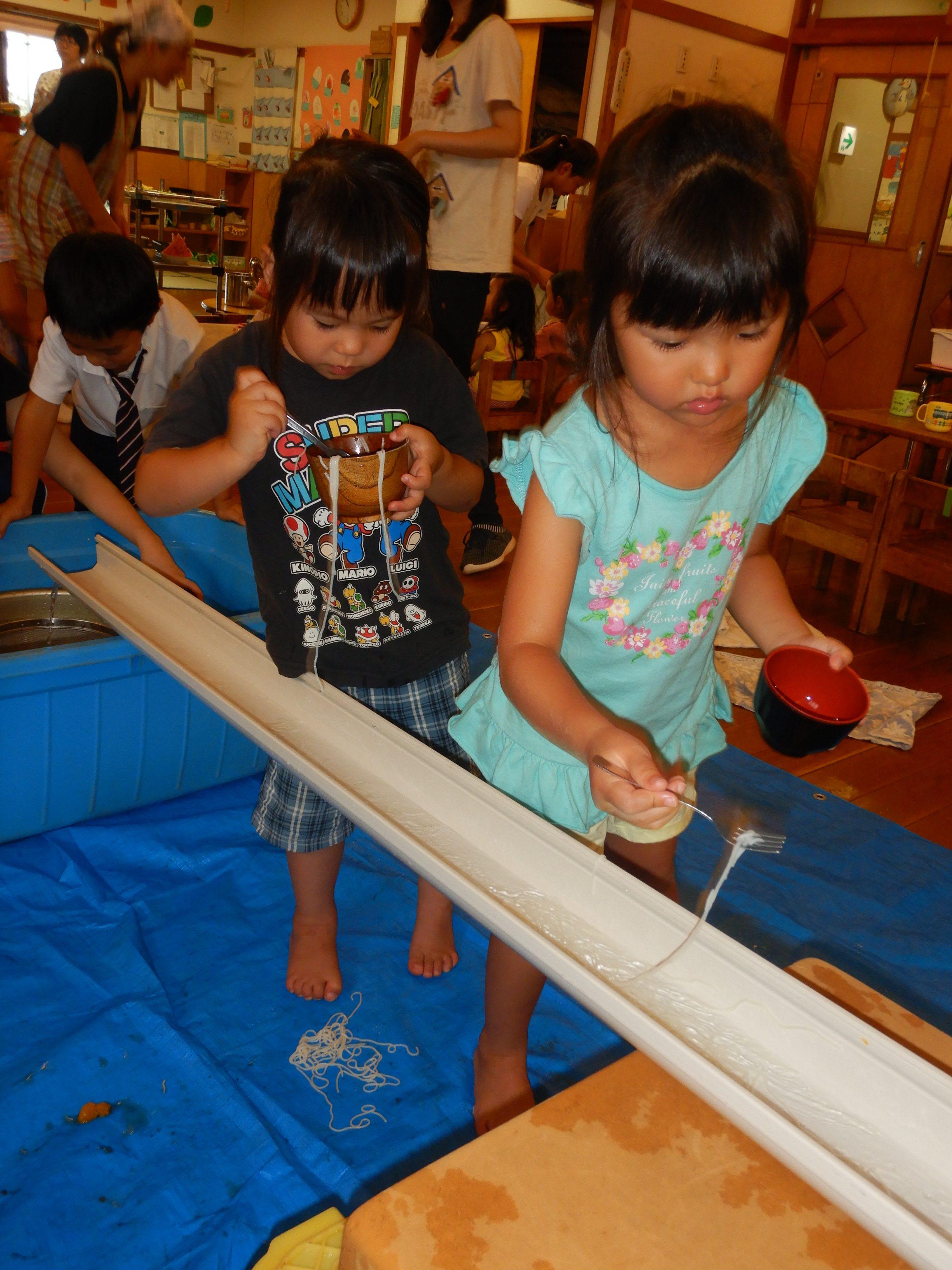 所沢市のあかねの風保育園で流しそうめんをしている子どもの画像